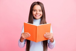 Portrait of charming content cheerful brainy brown-haired girl reading academic book isolated over pink pastel color background