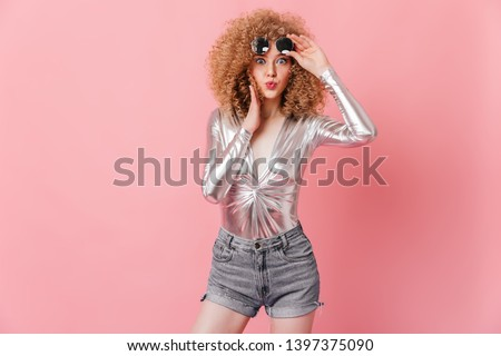 Portrait of charming curly blonde with blue eyes taking off her sunglasses. Woman in shiny top and shorts looks at camera in surprise on pink background