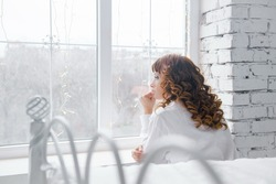 Portrait of charming girl sitting on windowsill and looking through window. winter day, white interior. Young woman looking in window in loft apartment.