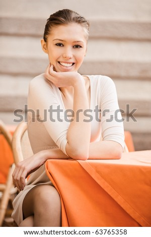 Portrait of charming girl which sits at little table in cosy cafe.