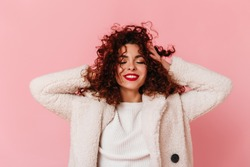 Portrait of charming lady with red lipstick and snow-white smile dressed in bright eco-coat and touching her curly hair on pink background