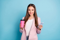 Portrait of charming lovely girl using her cellphone chatting with friends holding mug wearing white t-shirt isolated over blue background