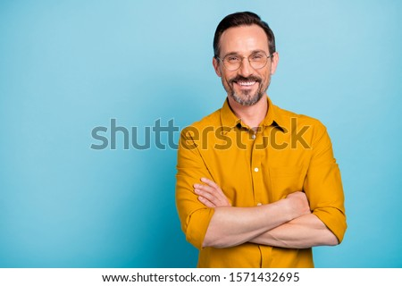Portrait of charming mature man true boss feel content emotions wear yellow shirt isolated over blue color background