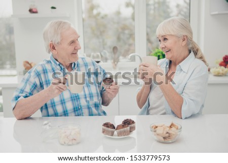 Portrait of charming people hold hands beverage hot pastry confectionery have brunch grey hairstyle sit table kitchen indoors