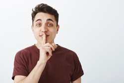 Portrait of charming playful male student in casual trendy t-shirt, lifting eyebrown with happy friendly expression, saying shh while showing shush with forefinger over mouth, smiling curiously