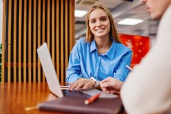 Portrait of charming positive hipster girl dressed in casual wear smiling at camera while sitting at laptop computer and searching information on website using wireless internet connection