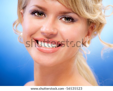 Portrait of charming smiling blonde on dark blue background