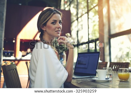 Portrait of charming smiling businesswomen posing while resting after work on her portable laptop computer during coffee break, young pretty female using net-book while sitting in modern cafe interior
