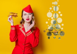 Portrait of charming vintage stewardess wearing in red uniform with airplane. Isolated on yellow background.