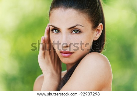 portrait of charming, young, naked woman, holding her hand beside her cheeks background summer green park