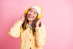 Portrait of charming young person listen to nice music touch headphones closed eyes isolated on pink color background