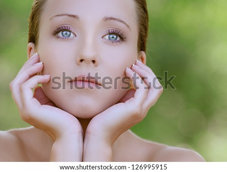 Portrait of charming young woman close up with bared shoulders, against background of summer green park.