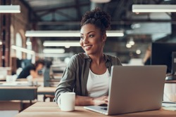 Portrait of charming young woman sitting at table with laptop and cup of coffee. She is looking away and smiling