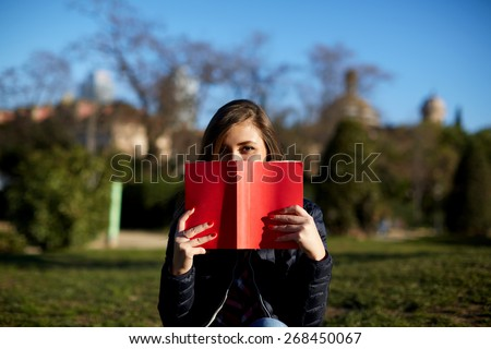 Portrait of charming young woman with red book held up close to her face, cute female covering half face with a book while sitting in the park at sunny afternoon