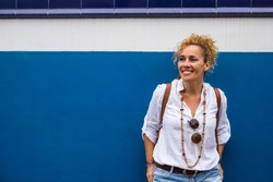 Portrait of cheerful adult blonde woman and blue and white wall in background
