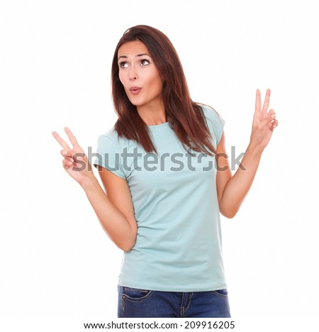 Portrait of cheerful adult woman on blue jeans celebrating her victory while looking to right up and standing on isolated white background - copyspace