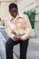 Portrait of cheerful African-American man in warm jacket reading guidebook