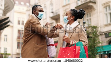 Portrait of cheerful African American young man and woman in medical masks with xmas presents meeting on street after holiday shopping and kindly speaking while snowing. Friends greeting with elbows