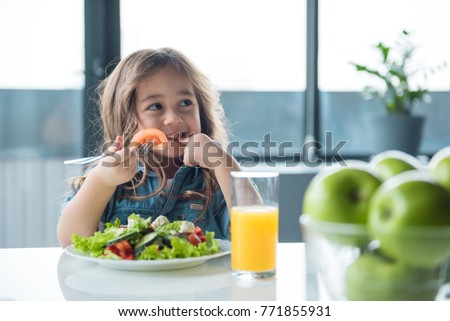 Portrait of cheerful asian girl eating salad with joy. She is looking aside with curiosity and smiling