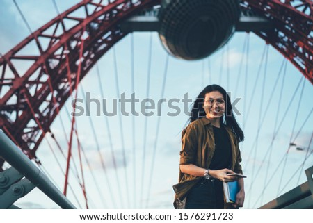Portrait of cheerful asian hipster girl in trendy outfit using mobile phone while walking on modern constructed bridge, cheerful female traveler looking at camera enjoying roaming 4G internet