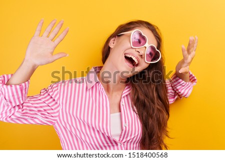 Portrait of cheerful Asian Kazakh young woman dressed casual and glasses smiling joyfully, laughing and fooling around on yellow background, girl enjoys summer holidays, vacation #1518400568