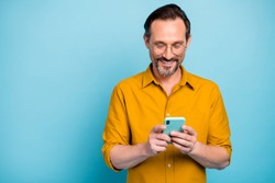 Portrait of cheerful attractive mature man modern device user use his smart phone type social network message wear good looking clothes isolated over blue color background