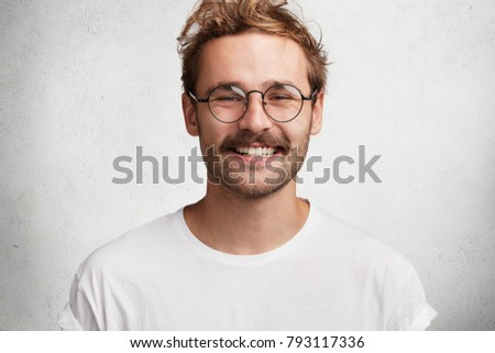 Portrait of cheerful attractive young man with stylish hairdo, pleasant pleased broad smile, dressed casually, has happy expression after realizing positive news, poses against white background. #793117336