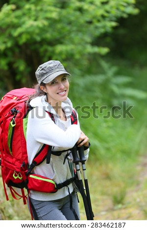 Portrait of cheerful backpacker in forest
