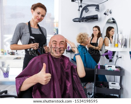 Portrait of cheerful bald man satisfied with service in professional barbershop