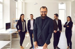 Portrait of cheerful bearded businessman, charismatic startup founder, with group of employees. Happy young leader in glasses with team of workers in background, smiling and looking at camera