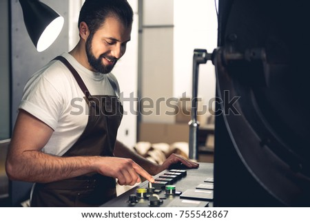 Portrait of cheerful bearded male master pressing button on special equipment for creating coffee. Technical appliance concept #755542867