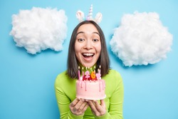 Portrait of cheerful beautiful Asian woman blows candles on birthday cake wears unicorn headband makes wish has happy festive mood isolated over blue background clouds white above. Festivity concept