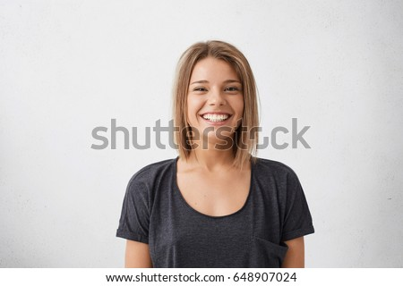 Portrait of cheerful beautiful woman with trendy hairdo having dark charming eyes and engaging smile posing in studio over white background. People, happiness, emotions and lifestyle concept