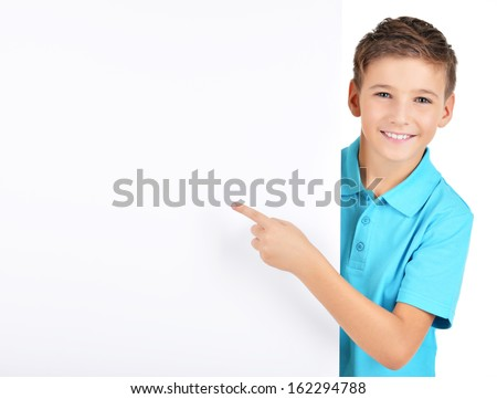 Portrait of  cheerful boy pointing on white banner - isolated on white background