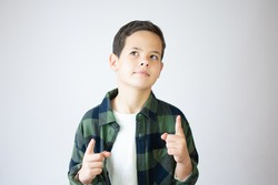 Portrait of cheerful boy with good idea - isolated over white background. 10 year old kid pointing finger up. Child points by finger upward. Cheerful boy shows something