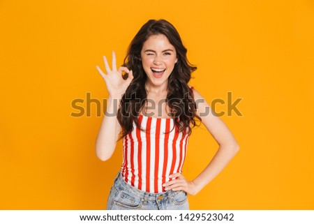 Portrait of cheerful brunette woman in striped t-shirt winking at camera and showing ok sing isolated over yellow background