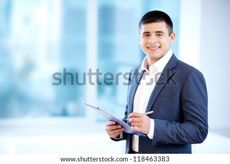 Portrait of cheerful businessman making notes and looking at camera