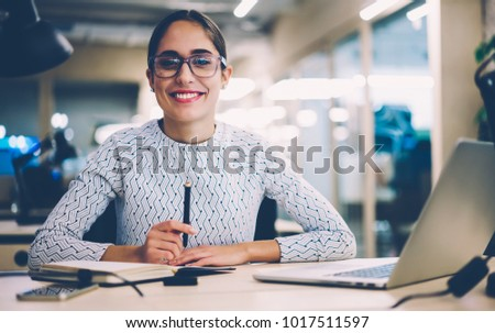 Portrait of cheerful businesswoman satisfied with occupation sitting at desktop in office with modern technologies,smiling female designer happy about accomplished creative project looking at camera #1017511597