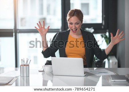 Portrait of cheerful businesswoman waving arms while looking at notebook computer. Career and enthusiasm concept #789654271