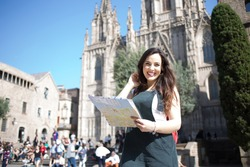 Portrait of cheerful caucasian female traveler excited with interesting vacations exploring european city, smiling beautiful woman 20s standing on square holding map for navigate and get to landmarks
