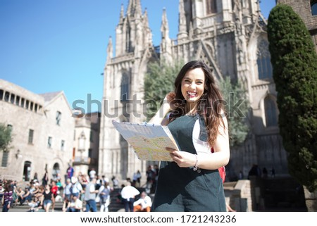 Portrait of cheerful caucasian female traveler excited with interesting vacations exploring european city, smiling beautiful woman 20s standing on square holding map for navigate and get to landmarks ストックフォト ©