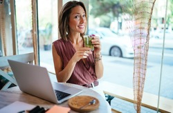 Portrait of cheerful caucasian woman blogger sitting with laptop computer at cafe interior having break drinking cocktail, prosperous female freelancer satisfied with remote job and business online
