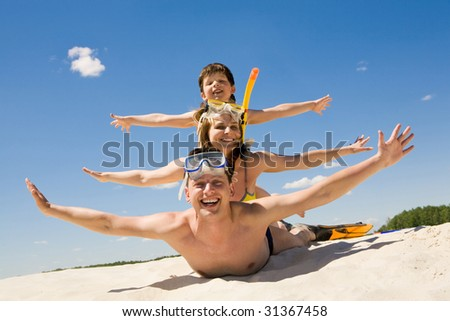 Portrait of cheerful couple and their son lying on sand and looking at camera