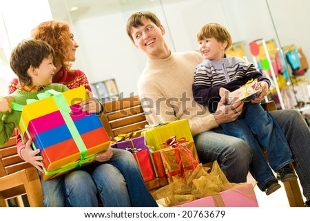 Portrait of cheerful couple and their two sons sitting in supermarket with presents near by