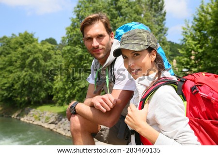 Portrait of cheerful couple of hikers on bridge