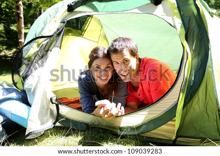 Portrait of cheerful couple relaxing in camp tent - stock photo
