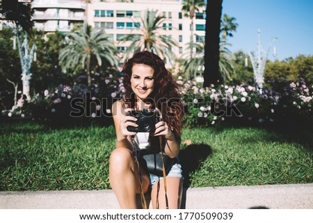 Photo of Portrait of cheerful curly brunette female photographer sitting on square in downtown on sunny day holding camera, smiling skilled woman traveler enjoying taking pictures during vacations tour