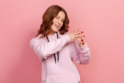 Portrait of cheerful curly haired teenage girl in hoodie showing hashtag symbol with fingers, smiling at camera, internet popularity. Indoor studio shot isolated on pink background