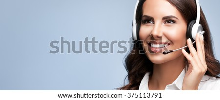 Portrait of cheerful customer support female phone worker, looking up, with copyspace, on grey background. Consulting and assistance service call center.