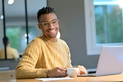 Portrait of cheerful ethnic guy working from home and having a coffee break